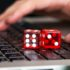 Close-up of red game dices on laptop with hands in background