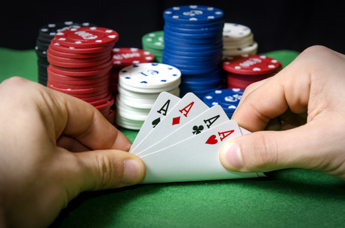 Hands in the foreground with Poker aces
