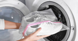 Woman putting mesh with white sneakers into washing machine, closeup